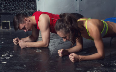 fit sportive man and woman doing plank core exercise training ba